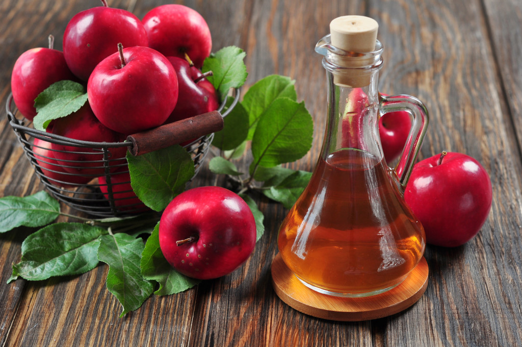 Apple cider vinegar in glass bottle and basket with fresh apples ** Note: Shallow depth of field