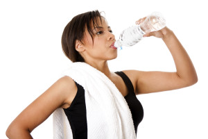 Beautiful attractive young sweaty woman drinking water after exercise workout, rehydrating thirst quenching, isolated.